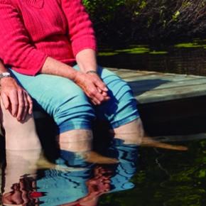 Parella de persones grans amb els peus a l'aigua